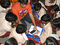 Volunteers helping the students to operate the tablet