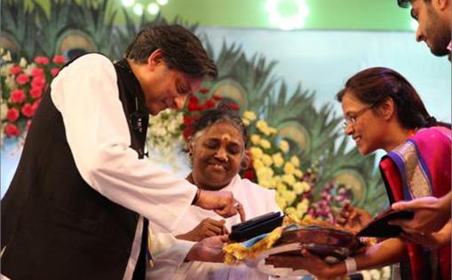 Shashi Tharoor writes on a tablet computer with the help of Mata Amritanandamayi Devi at Amritavarsham 60 Celebrations